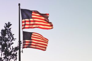 a modern american flag hanging over one with an 18th century design