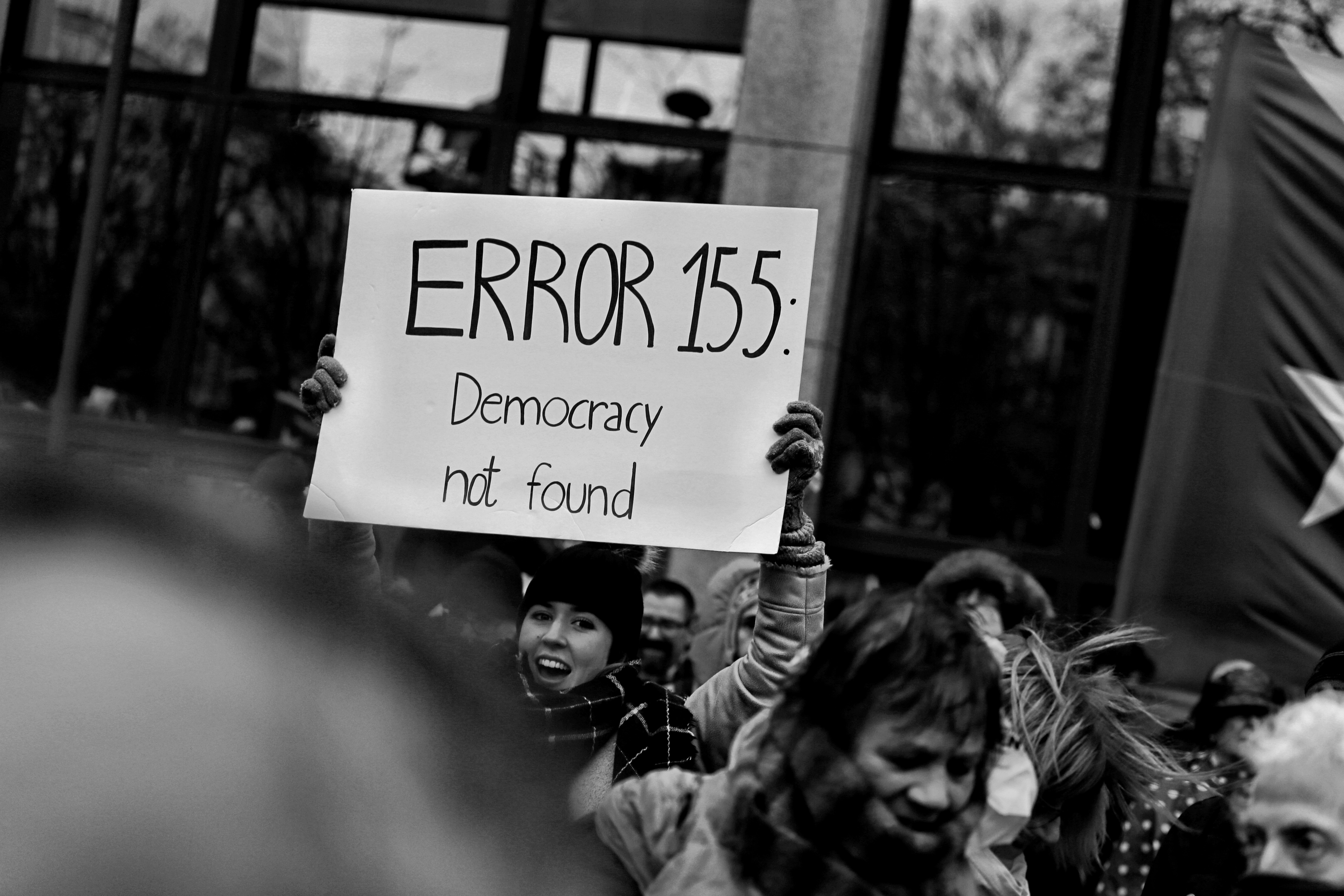 "Woman holding sign saying ""ERROR 155: Democracy not found"""